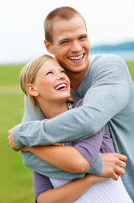Young couple hugging each other while laughing.
